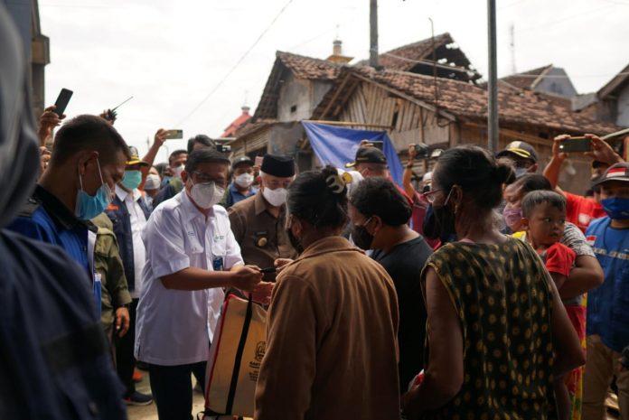 Dirut PG (baju putih membawa tas paket bantuan) mengunjungi daerah korban bencana Gempa Malang, Jawa Timur untuk menyerahkan bantuan paket sembako