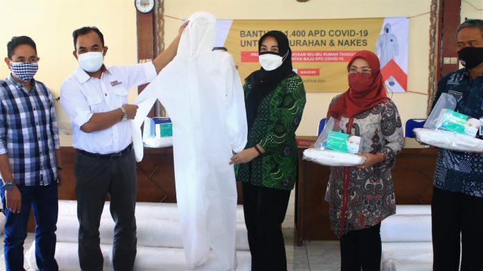 General Manager of CSR Edy Saraya (kedua kiri) menyerahkan bantuan baju hazmat kepada Lurah Sidomoro Christina Triandajani (ketiga kanan) di Pendopo Kelurahan Sidomoro, Gresik (5/8)